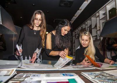 Anna, Emese and Aleksandra looking over the sketch books